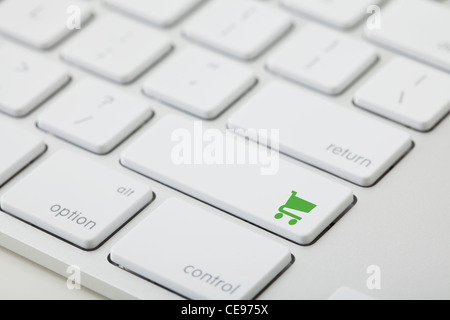 Computer keyboard with shopping cart icon on key - Stock Photo