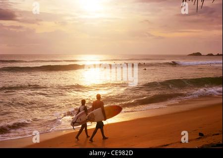 Couple of surfers walks along the beach in Hikkaduva - is the second best surf paradise in Sri Lanka - Stock Photo