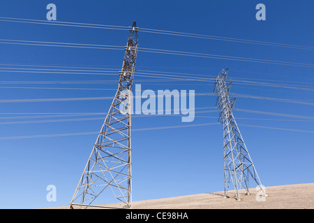 Electricity pylons against blue sky - California, USA - Stock Photo