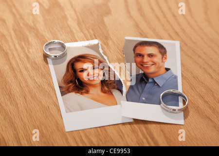 Studio shot of photo of couple torn in half and wedding rings - Stock Photo