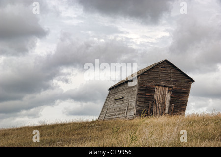An old western grainery on a hill with storm clouds in the background. - Stock Photo