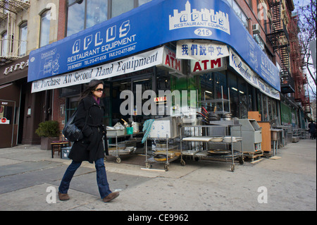 A woman walks past a restaurant supply seller on the changing Bowery in New York - Stock Photo