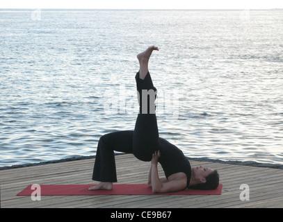 Yoga Pose Woman doing Setu Bandha Sarvangasana (Bridge Pose Variation) with the ocean behind. - Stock Photo
