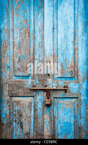 Old locked blue wooden doors on a rural indian village house. India - Stock Photo