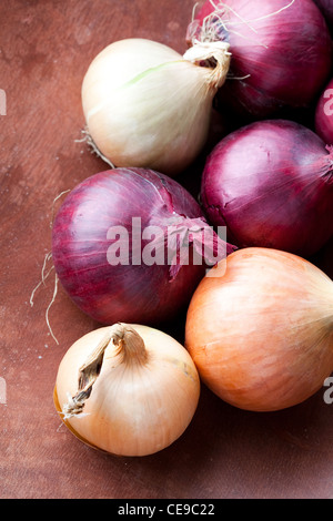 Close-up of red and yellow onions on a wooden background - Stock Photo