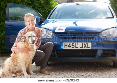 Portrait of smiling young woman with dog in front of car with learner's permit - Stock Photo