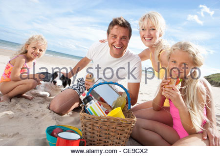Portrait of smiling family with dog picnicking on sunny beach - Stock Photo