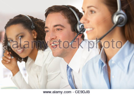Smiling business people wearing headsets - Stock Photo