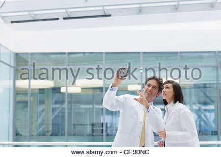 Engineers in lab coats examining part in office - Stock Photo