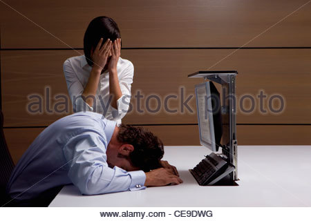 Exhausted businessman and businesswoman at desk in office - Stock Photo