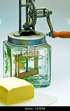 butter churn with a piece of butter - Stock Photo