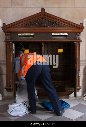 Postman collecting the post from an old-fashioned, wooden post box at the The Royal Academy of Arts, Piccadilly, - Stock Photo