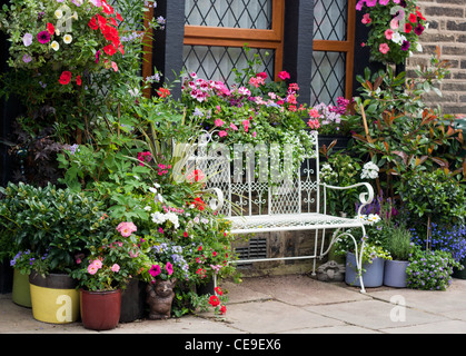 Beautiful white wire bench among flowers - Stock Photo