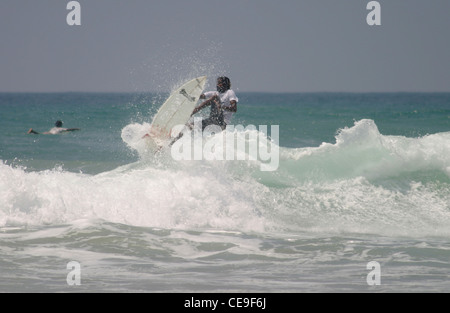 Local Sri Lankan Surfers ride the waves in Hikkaduwa at Main Reef, South West Sri Lanka - Stock Photo