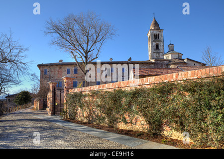 Ancient abandoned abbey and old church behind brick wall in town of La Morra, Northern Italy. - Stock Photo