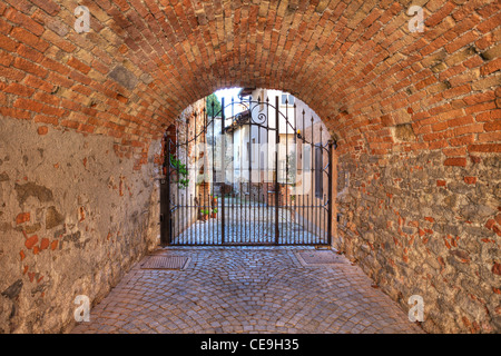 Old brick arched passage leading towards metal gate at the entrance to courtyard in La Morra, Italy. - Stock Photo
