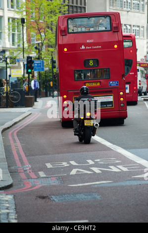 Rear view of a motorcyclist and a bus in traffic in the centre of the City of London. - Stock Photo