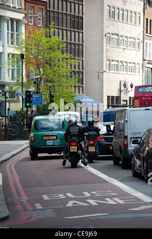 Rear view of motorcyclists and a taxi in traffic driving through the centre of the City of London. - Stock Photo