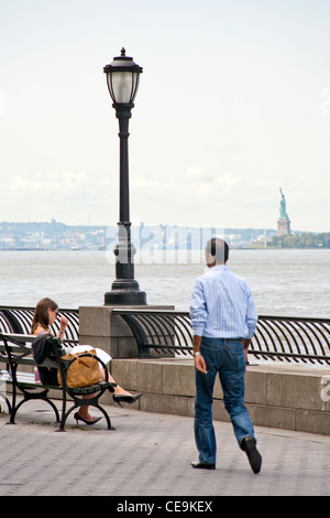 A woman sits on a bench and a man walks by the Hudson Bay and Hudson River with the Statue of Liberty visible in - Stock Photo