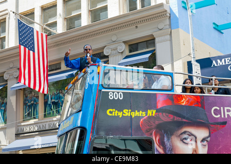 A tour guide on a bus gives a talk to tourists in New York City. - Stock Photo
