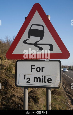 Highway code triangular traffic sign slippery road ahead for half a mile - Stock Photo
