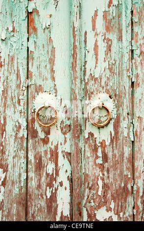 Old wooden door with paint peeling from it, Ayvalik, Turkey - Stock Photo