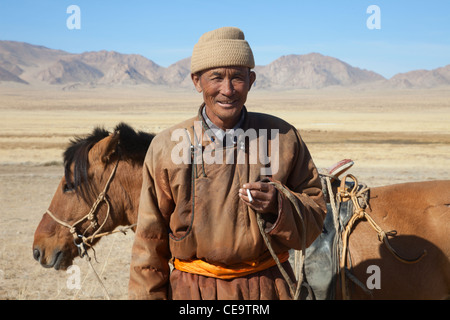 Nomad with his faithful horse in the steppes of Mongolia - Stock Photo