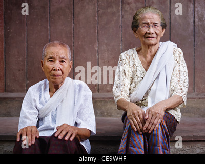 Portrait of two old asian women sitting against brown wall and looking at camera