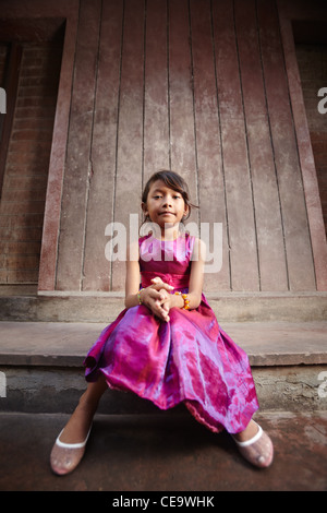 Portrait of cute Asian female child in pink dress looking at camera - Stock Photo