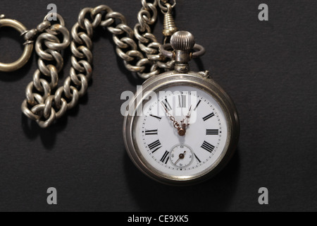Vintage pocket watch with chain on black background - Stock Photo