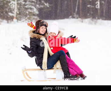 happy family; mother and daughter with the sledge outdoor on a winter day - Stock Photo