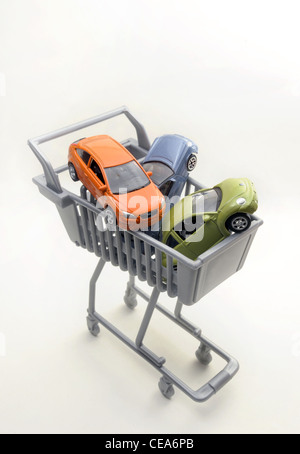 MODEL CARS IN SUPERMARKET SHOPPING TROLLEY RE CAR BUYING BUYERS INTERNET INSURANCE RISING PRICES MOTORING SHOPPING - Stock Photo
