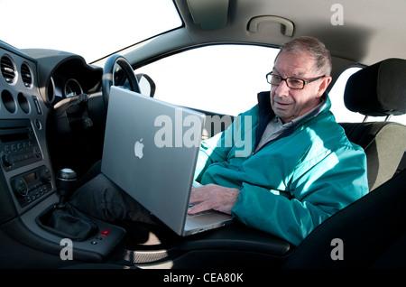 senior man using laptop computer in car - Stock Photo