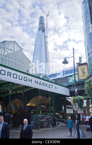 The Shard construction building giant crane towering over the Borough Market sign & canopy & new train bridge to - Stock Photo