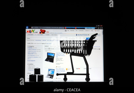 COMPUTER SCREEN WITH SHOPPING TROLLEY PARCELS RE INTERNET SHOPPING EBAY  ONLINE BUYING BUYERS FRAUD INCOME  ECONOMY - Stock Photo