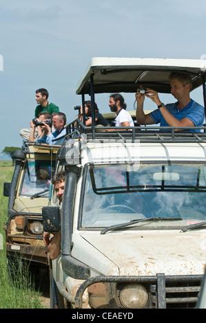 Tourist watching wildlife from their cars at Maasai Kopjes in Serengeti, Tanzania - Stock Photo