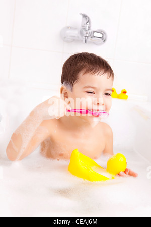cute four year old boy taking a bath with foam and brushing teeth - Stock Photo