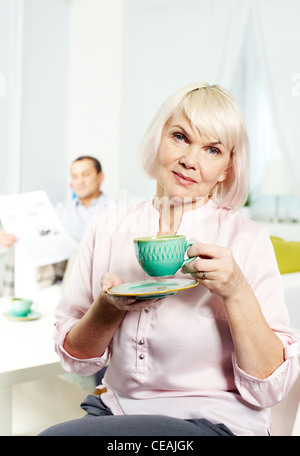 Portrait of mature woman with cup looking at camera on background of her husband - Stock Photo