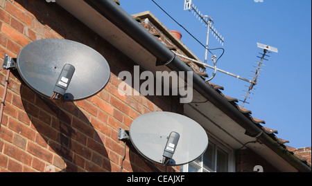 Satellite dishes TV aerials on houses - Stock Photo
