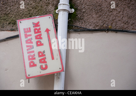 Private car park sign hanging on side so direction arrow points up to the sky. - Stock Photo