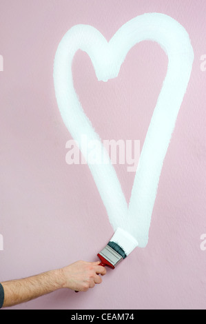 person paints a heart on a pink wall - Stock Photo