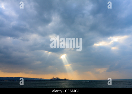 Crepuscular rays, sunlight streams through small holes in the clouds, Danshui River, Taipei, Taiwan - Stock Photo