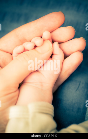Mother holding hand of baby - Stock Photo