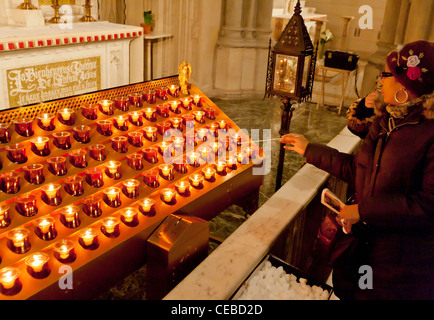 A person lights a candle in a church. - Stock Photo