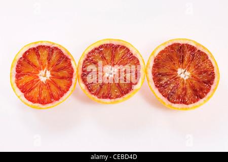 Citrus x sinenesis. Three blood orange halves on a white background. - Stock Photo