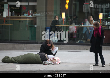 Woman check on homeless man on pavement with his pet in downtown Toronto - Stock Photo