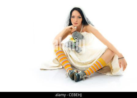 funny young brunette bride wearing old sporting shoes with a toy in her hands - Stock Photo