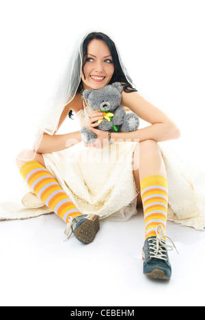 funny dreamy beautiful bride wearing old running shoes and holding a toy in her hands - Stock Photo
