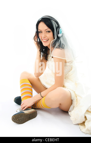 happy young brunette bride wearing earphones and sporting shoes - Stock Photo