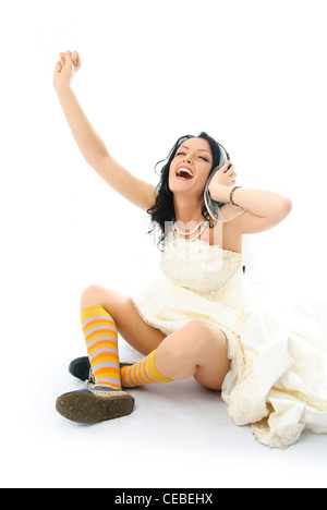 happy young brunette bride wearing sporting shoes and listening to the music - Stock Photo